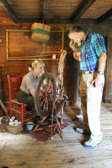 Jackie explains the mechanics of spinning to Brinegar Cabin visitors